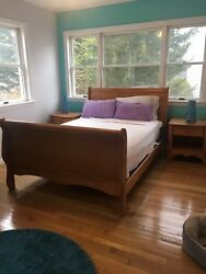 sleigh Bedroom Set With A Full Bed, Two Night Tables, A Dresser And A Mirror.