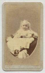 Photograph Infant In White Dress Sitting On Cushion Cheeks Highlighted With Pink