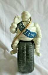 Cast Iron Michelin Man Sitting On A Tire With Hose Blowing Up The Tire.