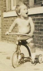 Yelling Shirtless Boy On Tricycle. 1940s.