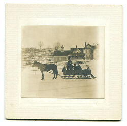 Horse Drawn Winter Sled With Riders, Farm And House In Background.