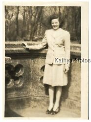 FOUND Bamp;W PHOTO G 9376 YOUNG WOMAN STANDING IN FRONT OF A WALL TREES IN BACK