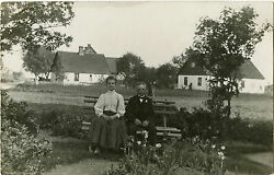 Village Scene With Boy And Girl Sitting On Bench And Vintage Real Photo Postcard