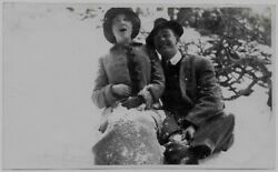 Old Photo Woman And Man Sitting In Snow Wearing Coats And Hats 1910s