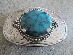 Faux turquoise stone set in a chrome plated belt buckle worn by a man