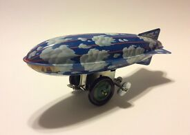 vintage windup tin toy blimp sky and clouds