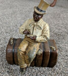 RARE ANTIQUE CAST IRON DOOR STOP by JUDD- Black man sitting on a cotton bale -