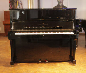 A 1985 Steinway Model V upright piano with a black case and brass fittings