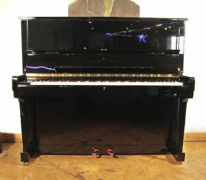 A 1995 Steinway Model K upright piano with a black case and brass fittings