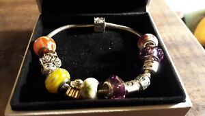 Authentic Pandora Sterling Silver Bracelet With Charms in original box.