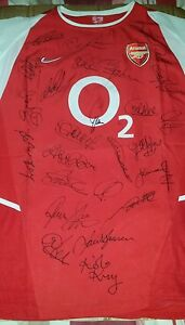 Arsenal signed shirt tagged Nike XL by 24 former players and current manager.