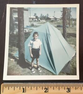 Vintage photo picture photograph of a boy camping standing next to a tent