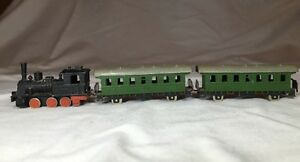 cast iron train locomotive and two passenger cars
