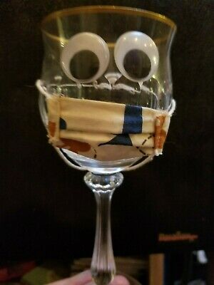 crystal goblet with googlie eyes and mask