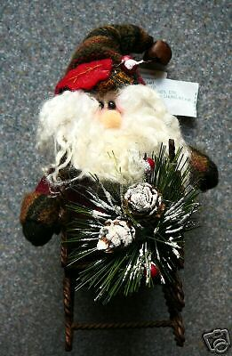 Cloth and metal Santa Claus in sleigh with pine cones