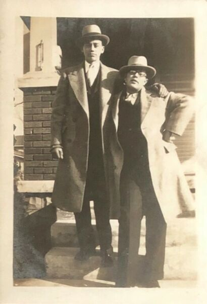 Snapshot two men wearing hats stand on stoop arms around each other 1940s