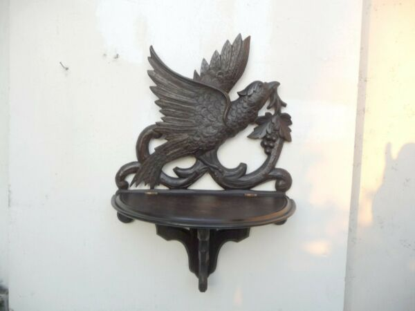 AN ANTIQUE DECORATIVE BLACK FOREST CARVED WALL SHELF CRESTED BY A CAPERCAILLIE