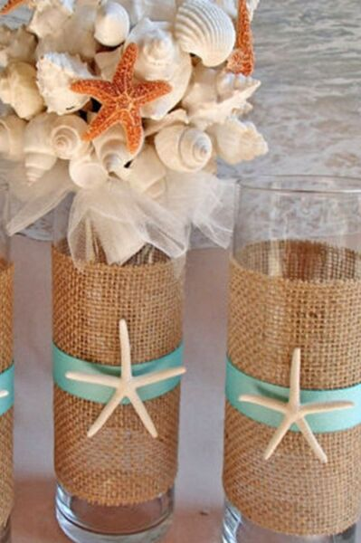Flower vase wrapped in burlap cloth decorated with starfish and colored ribbon