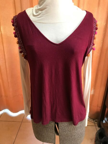 Sleeveless wine top with dingle balls on the sleeve opening