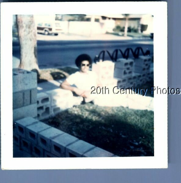 FOUND COLOR POLAROID K6740 BLACK MAN SITTING ON GRASS BY WALL