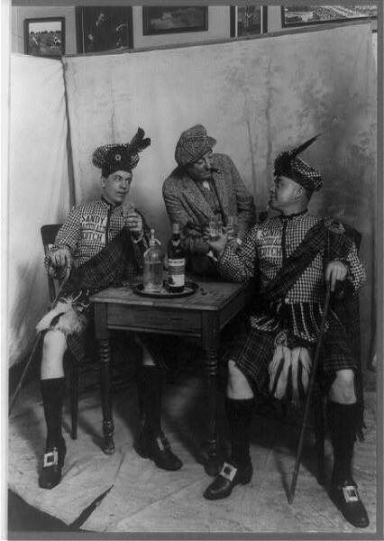 Two men wearing kiltssmall tabledrinking Sandy MacDonald scotchwhiskeyc1913