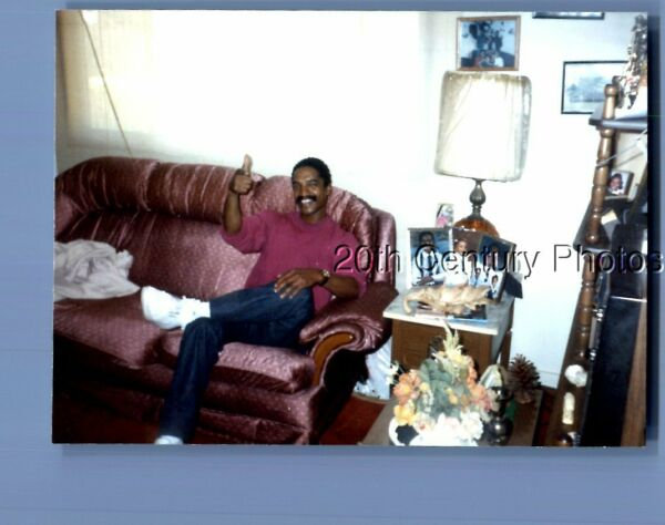 FOUND COLOR PHOTO P8217 BLACK MAN SITTING ON COUCH WITH THUMB UP