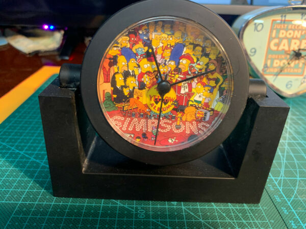 The Simpsons: Tilting black clock with The Yellow Album on its face
