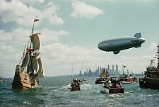 The Mayflower II enters New York Harbor escorted by boats and a US Navy blimp