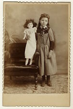 A YOUNG GIRL AND HER DOLL WITH MUSSED HAIR (CABINET CARD)