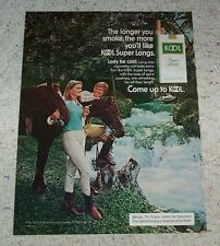 1975 ad page -KOOL Cigarettes- Pretty Lady in cowboy boots smoking Guy Horses AD