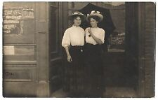 VTG PHOTO TWO YOUNG WOMAN BEAUTY w FLOWER HAT & UMBRELLA at SHOP DOOR 1915 RPPC