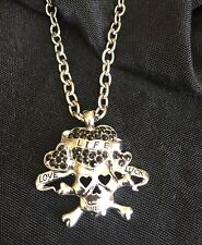 silver toned skull necklace with black stones