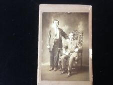 Antique photo of two young men, one sitting in nice mahogany chair