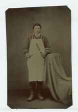 OCCUPATIONAL YOUNG BUTCHER WEARING APRON AND HOLDING KNIVES. TINTYPE, TINTED.