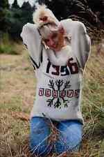 690022 girl avec jeans et pull kneeling in grass A4 papier photo