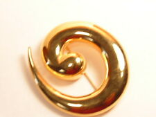 Gold colored Monet fashion pin with a smooh, modern design