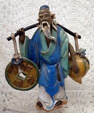 CHINESE MUD MAN YOKE BEARER WITH COIN AND PEACH FIGURINE EARLY 20TH CENTURY