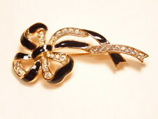 Black enamel and gold colored pin accented with white crystals