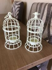 A PAIR OF WHITE METAL BIRD CAGE TEA LIGHT HOLDERS