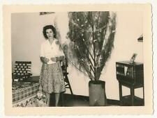 Young woman standing by Christmas tree and old radio - vintage photo