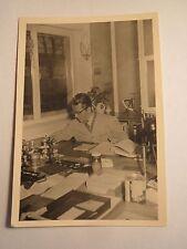 Mann mit Kittel der Firma Bucher sitzt am Schreibtisch - Stempel Ordner / Foto