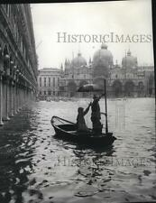 1964 Press Photo Wife protects man as he ferries St Mark's Square during flood