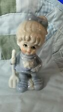 5 inch porcelain  girl with rake/shovel in blue and white