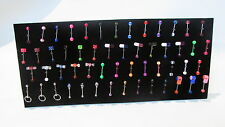 Display stand full of tongue bars body jewellery, whistles skull pill dice etc
