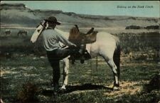 Cowboy Mounting His Horse TAKING UP THE BACK CINCH c1910 Postcard