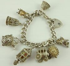 Vintage Sterling silver charm bracelet with 8 charms and padlock closer.