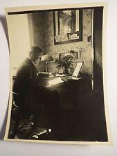 junger Mann sitzt am Schreibtisch und liest ein Buch - Postkarten am Bild / Foto