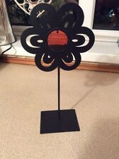 A BLACK METAL FLOWER TEA LIGHT HOLDER WITH A ORANGE CENTRE