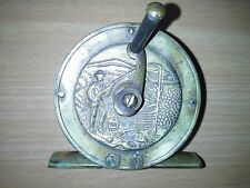 A brass reel with fishing scene