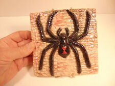 decorative ceramic tile with Spider on a wall; gallery/ studio label on reverse